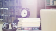 books and clock on table in library video
