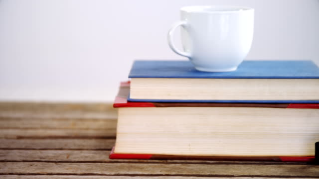 Books, coffee cup, and smart watch on wooden table 4k video