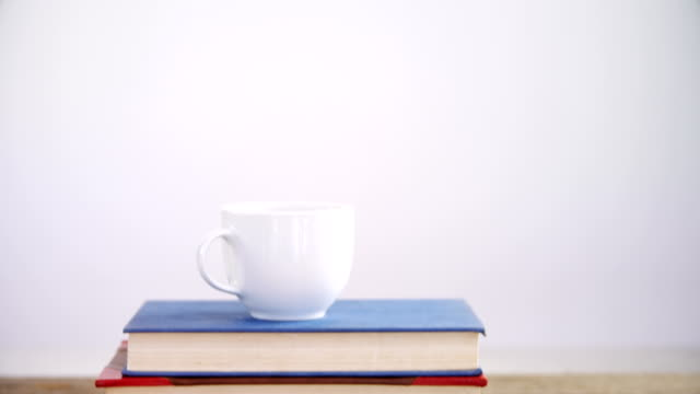 Books, coffee cup and spectacles on wooden table 4k video