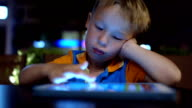 Bored little boy using pad in cafe video