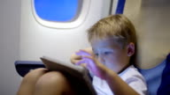 Bored or tired boy in plane using tablet computer video