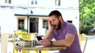 Bored, sleepy man drinks coffee browsing smartphone video