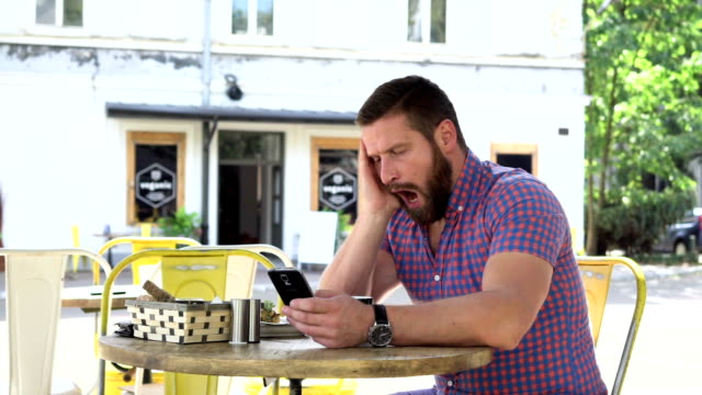 Bored, sleepy man drinks coffee browsing smartphone video