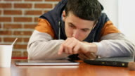 Bored student reading bad news on tablet, alone in cafe video