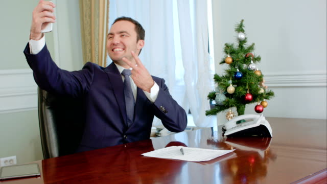 Boss taking funny selfies with New Year Tree, smiling video