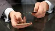 Boss using mobile banking on smartphone, inserting card number video