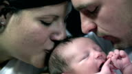 HD SLOW: Both parents kiss baby head at same time video