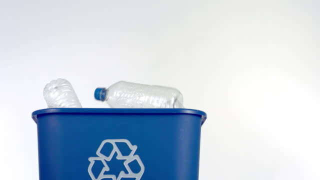 Bottle falling into recycle bin, slow motion video
