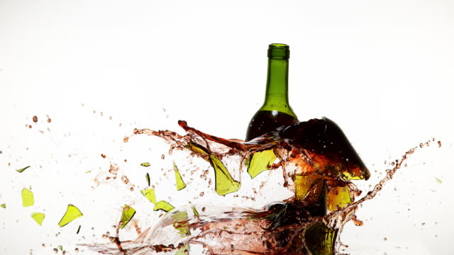 Bottle of Red Wine Breaking and Splashing against White Background, Slow motion 4K video