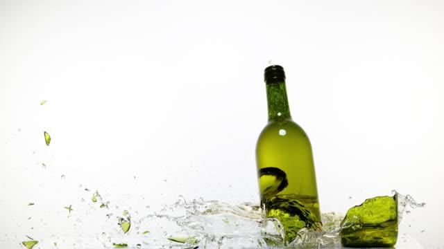 Bottle of White Wine Breaking and Splashing against White Background, Slow motion 4K video