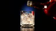 Bottle pours whiskey into a glass video