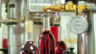 Bottles of red alcohol stoppered. In the foreground conveyor element - gauge video