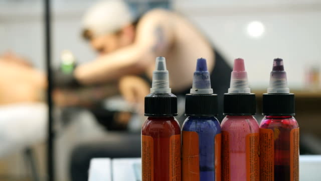 Bottles with colorful paints, the tattoo artist is working on blurred background video