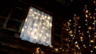 Bottom view on the window with shimmering garlands in a wooden house video