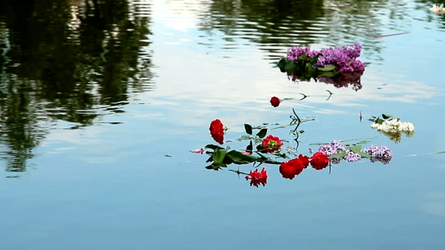 Bouquets of carnations and lilacs floating on the water video