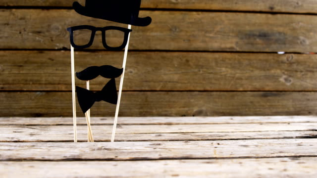 Bow tie, spectacles and fake mustache arranged on wooden plank video
