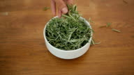 Bowl with rosemary on a wooden table video