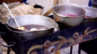 Bowls with delicious mulled wine cooking on charcoal, street vendor making food video