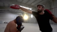 Boxer pad work session with trainer in an old building video