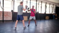 Boxer punching with his sparring partner at the gym video