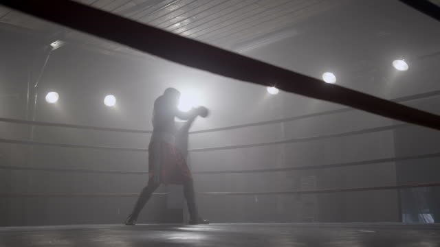 Boxer training in boxing ring, silhouette video