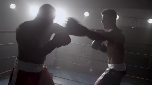 Boxers fight in boxing ring, silhouette video