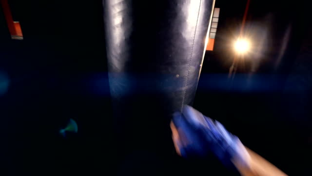 Boxing of the punching bag by unrecognised person. Close-up. 4K video