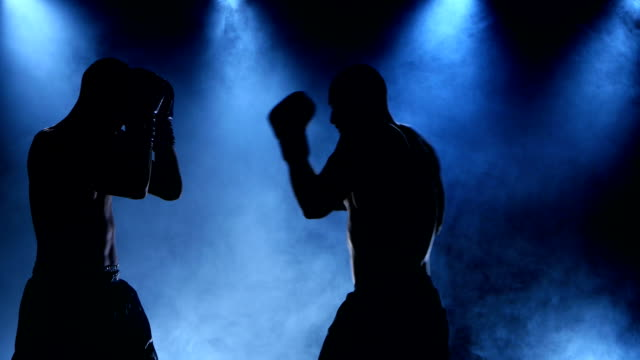 Boxing two young sportsman in a smoky studio in silhouette video