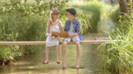 SLO MO Boy and girl sitting on footbridge and reading video