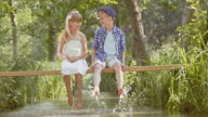 SLO MO Boy and girl sitting on footbridge splashing water video