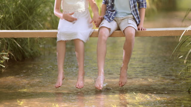 SLO MO Boy and a girl sitting on a footbridge splashing water with their feet video
