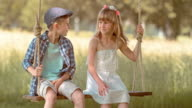 SLO MO Boy and a girl sitting on a swing and smiling video