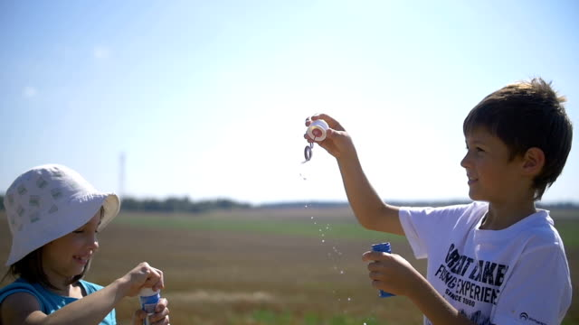 Boy And Girl Blowing Soap Bubbles In The Field, Slow Motion video