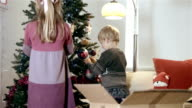 Boy and girl decorate Christmas Tree video