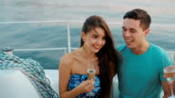 Boy and girl drink champagne on the yacht and having fun. video