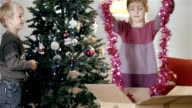 Boy and girl hang decorations on tree video