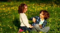 Boy and girl have fun on spring grass. video
