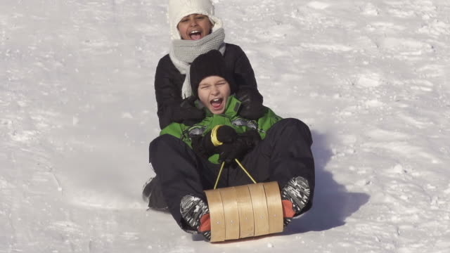Boy and girl have fun sledding video