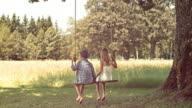 SLO MO Boy and girl holding hands sitting on swing video