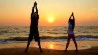 Boy And Girl Making Exercises On The Beach At Sunset video