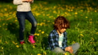 Boy and girl on spring grass. video