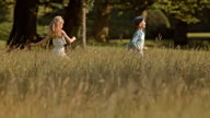 SLO MO TS Boy and girl running across a meadow video