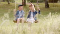 SLO MO DS Boy and girl sitting on a swing video