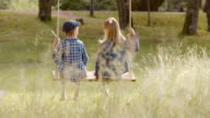 SLO MO DS Boy and girl swinging outside video