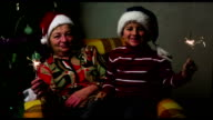 boy and grandmother in New Year's caps with sparklers on the background of Christmas tree video