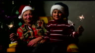 boy and grandmother in New Year's caps with sparklers sitting in a chair on the background of Christmas tree video