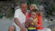 Boy and grandparents looking at photos on smartphone video