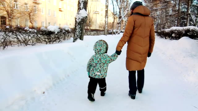 Boy and his mother are walking in the park. video