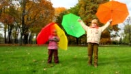 Boy and little girl rotates with umbrellas in autumn park video