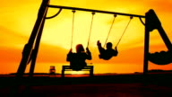 boy and woman on a swing at sunset video
